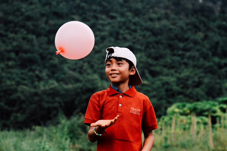 boy wearing a red shirt and tossing a pink balloon